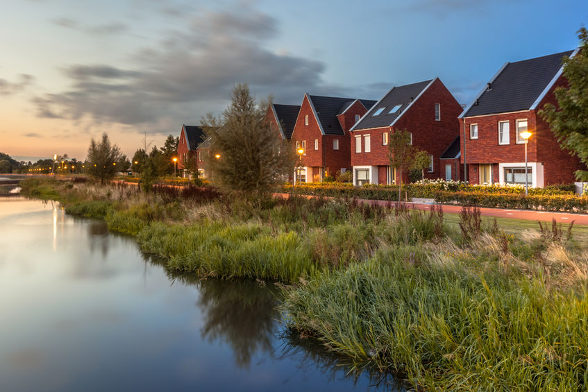 Long exposure night shot of a Street with modern ecological middle class family houses with eco friendly river bank in Veenendaal city, Netherlands.